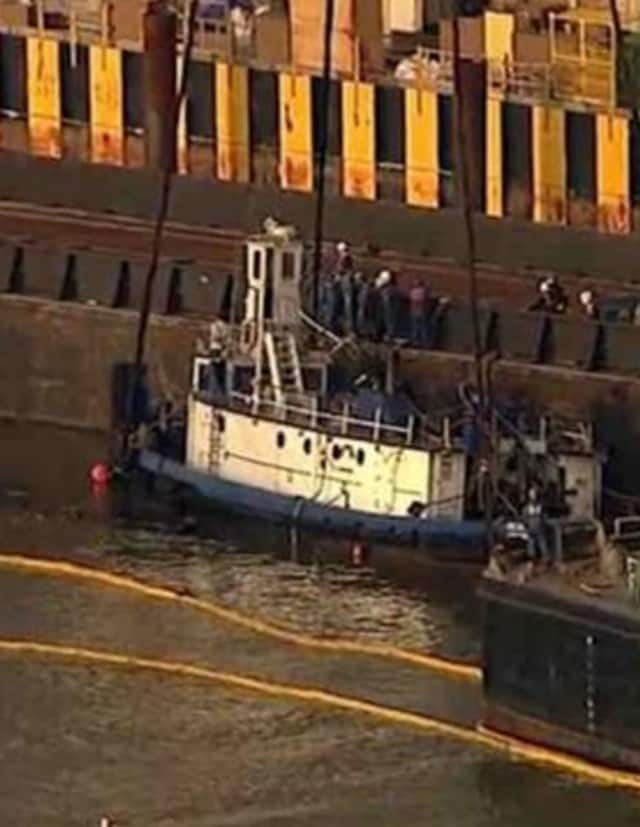 Salvage operations to remove the sunken tugboat.
