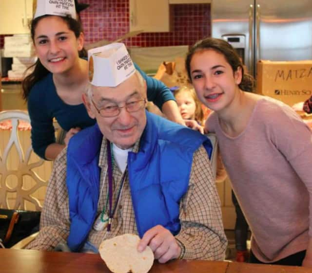 Ridgewood twin sisters Hanna and Nicole Kaplun, volunteers in Valley Chabad's Cteen program participate in the previous year's Passover event at the Bristal in Woodcliff Lake with Bernie Turner.
