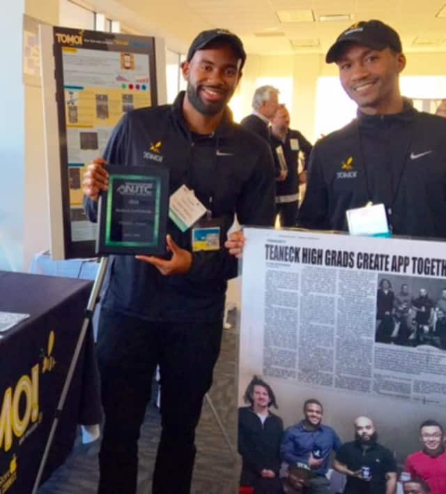 Teaneck High School graduate Alfonzo Smith, right, and a TOMO! team member proudly display their People's Choice Award.