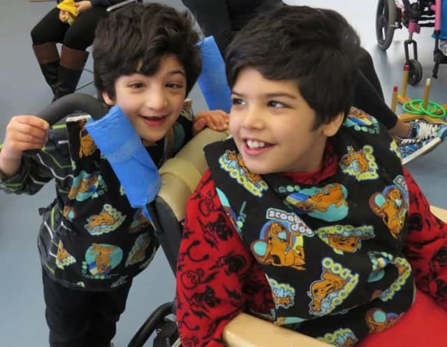 Brothers Yosuf (standing) and Sultan (seated) receive occupational, physical and speech therapies at the school program at Cerebral Palsy of Westchester.