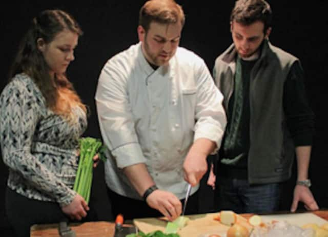 Aubrey Sierer '16, left, and Patrick Donegan '18, right, practice their cooking skills with Chef James DeSilvestri '07, center.