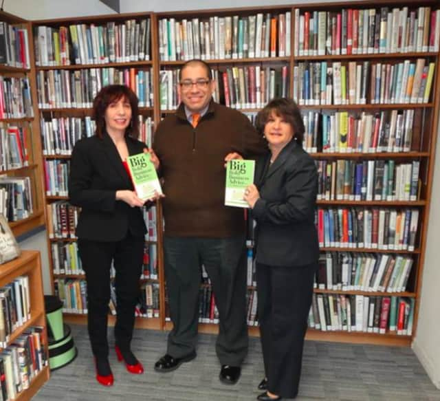 Joyce Restaino (left) and Maria-Elena Grant (right) present West Milford Township Library Director Ricardo Pino with copies of their book.