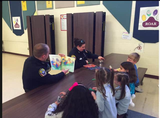 Bethel Police Officer Robinson and School Resource Officer Courtney Whaley read to children on story time night at Berry Elementary School in Bethel.