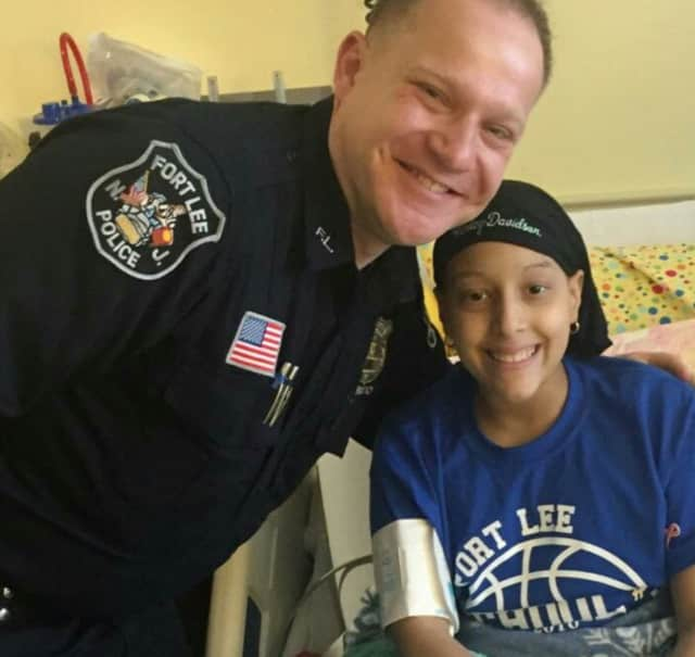Fort Lee Detective Nick Mircovich with Briana Lopez, 11, who has leukemia.
