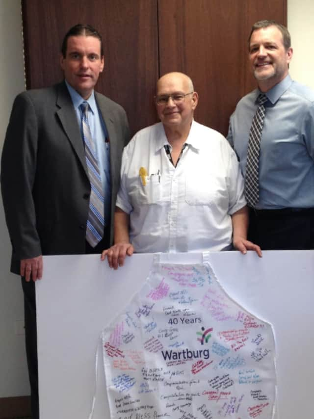 From left, Chuck Fox, senior director of Food Services for Morrison Senior Living, Frank Sciarpelletti, Wartburg head cook and David J. Gentner, Wartburg president and CEO, pose with honorary apron presented to Sciarpelletti for 40 years of service.