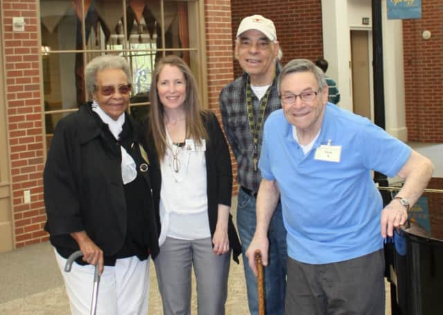 Anne Pelisson, second from left, is Supervisor of the Adult Day Program for the Waveny LifeCare Network in Network. Cora (left), Angel (second from right) and Jack are frequent visitors to the program.