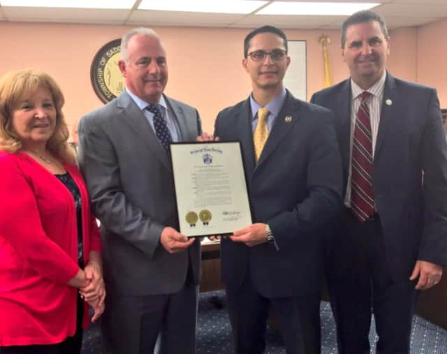 Assemblyman Joe Lagana (center right) presents a certificate to Saddle Brook Mayor Robert White (center left) to celebrate the township's 300th anniversary.