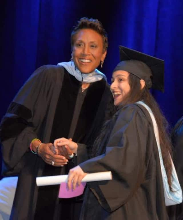 The College of New Rochelle commencement speaker Robin Roberts, left, shakes hands with new graduate Bianca Jeannot, a Bronx resident.