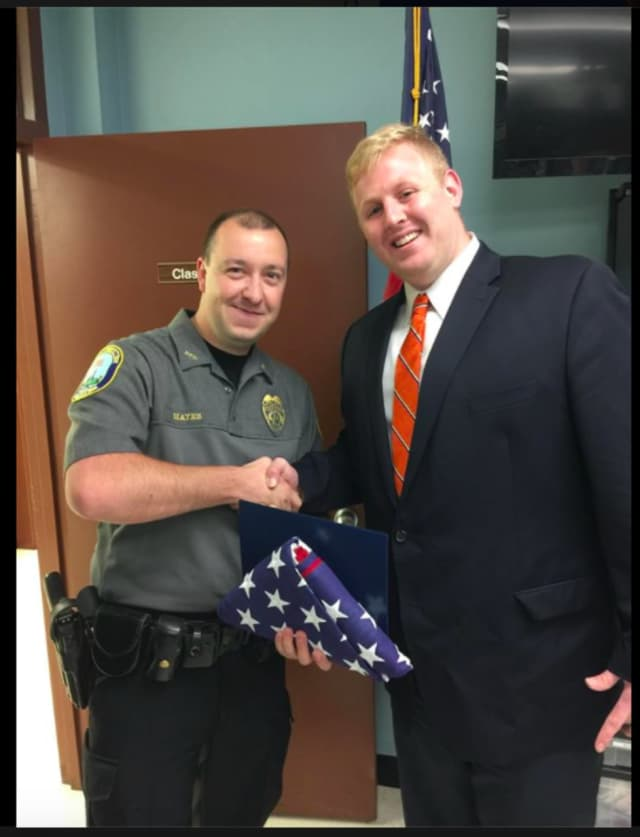Newtown Police Department Officer Matthew Hayes was presented with a flag that was flown over the Nation's Capitol by Mackenzie Demac from Congresswoman Elizabeth Esty's office.