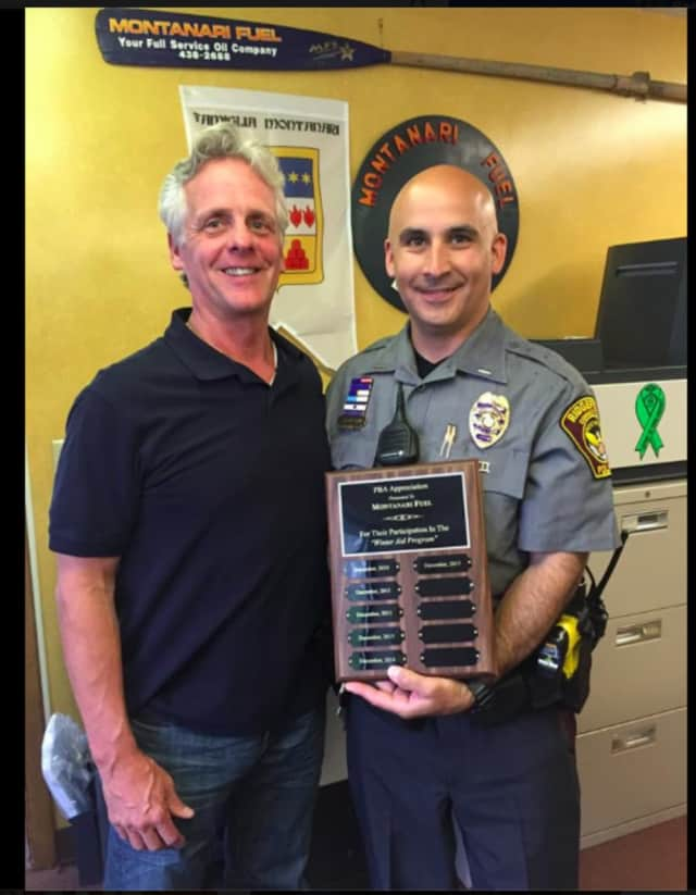 "From left, Andy Montanari Jr. and Ridgefield Lt. Jeff Raines. The Ridgefield Police Benevolent Association presented Montanari Fuel with a plaque of appreciation for assisting with the ""Winter Aid"" program since its start."