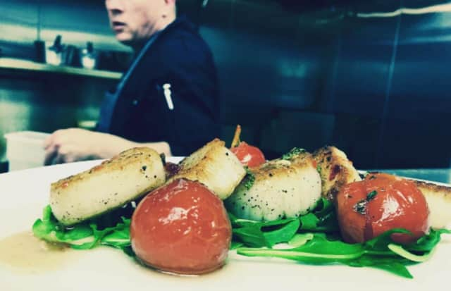 White Maple Cafe chef Bian McGackin whips up pan-seared scallops fresh from Montauk with tomatoes and mint. tossed in honey chili dressing and served on a bed of arugula.