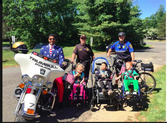 Trumbull police motor officer Scott Thompson and bicycle officer Michael Edwards celebrated Flag Day at the St. Vincent's Special Needs Center with a group of kids.