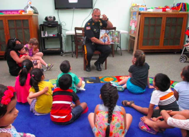 "East Rutherford Police Captain Phillip Taormina read ""Officer Buckle and Gloria"" to a group of youngsters this Monday."