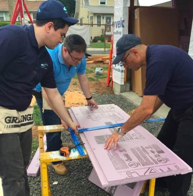 Cross River Bank employees draw up plans on Habitat Bergen's Bergenfield site.