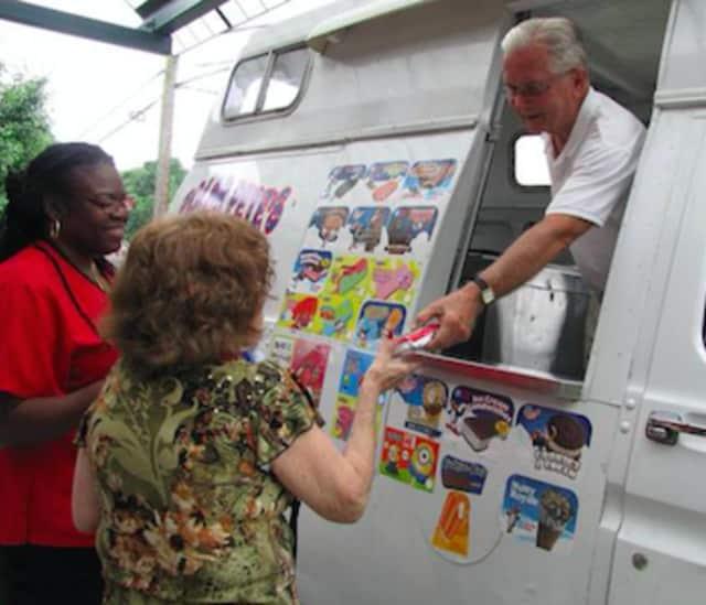 Jack of Polar Pete's Ice Cream hands a River House member an ice cream bar.