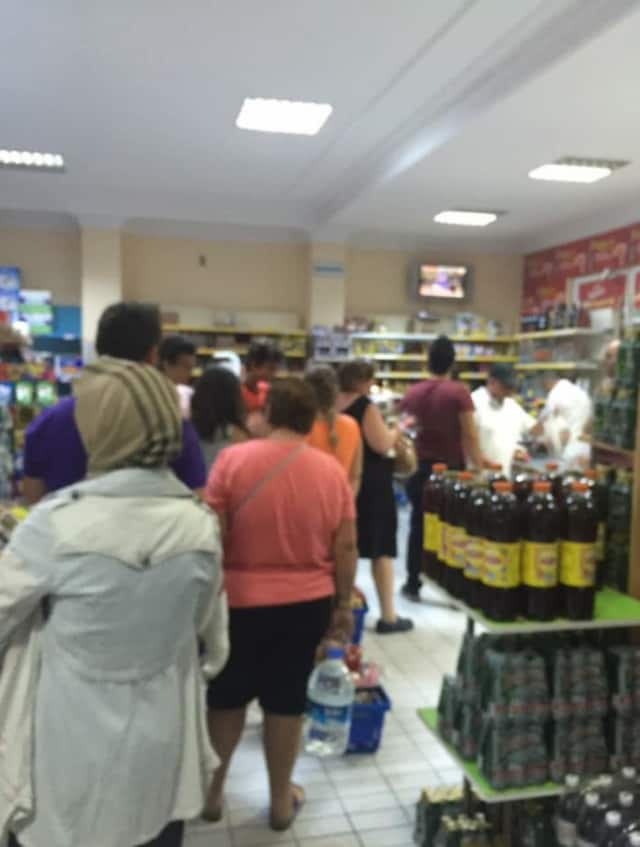 A supermarket crowd gathers to watch reports on the uprising at a supermarket in Turkey.