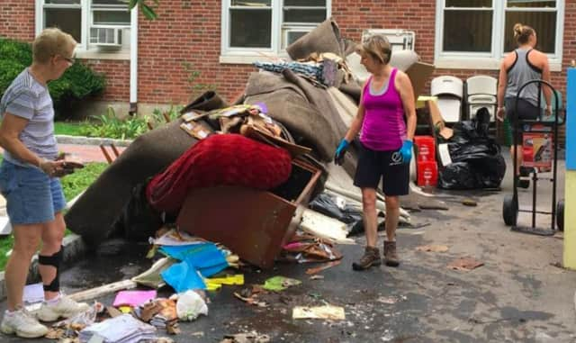 Volunteers work to clean Packanack Community Church, which was damaged in a flood on Monday.