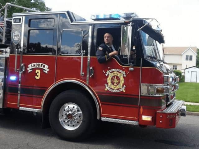 A Saddle Brook firefighter rides in an engine.