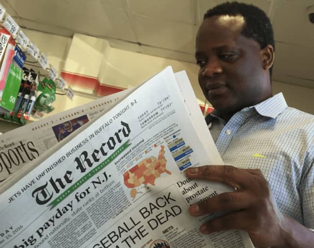A Bergen Record reader checks out Thursday's paper in 7-Eleven on Passaic Street in Hackensack.