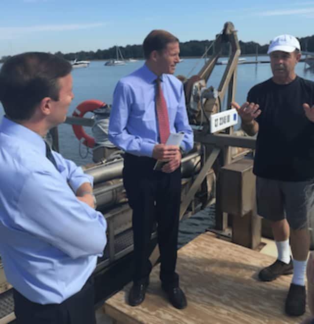 Commercial fisherman Ed Stilwagen explains clamming to U.S. Senators Chris Murphy, left, and Richard Blumenthal, center, at Greenwich Point on Friday.