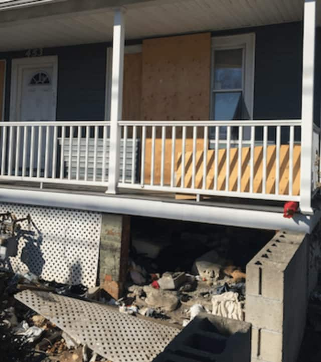 A mattress can just be barely seen under a porch of an abandoned home where a Guatemalan man was found dead Wednesday morning in Stamford. Police say there were no signs of foul play or trauma and believed death due to a medical issue.