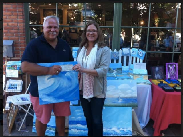Darien artist Peter Saverine presents a donation for the Darien Arts Center to Amy Allen, DAC executive director.