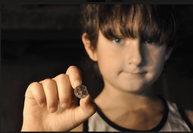 Jake Lattanzi, 8, displays Spanish silver coin (circa 1773-89) he found in Monroe with his dad.