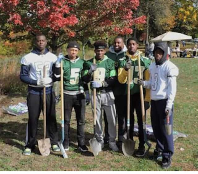 Bassick Lions football team members joined with other volunteers for a recent Saturday project to improve the Pequonnock River riverbank at Glenwood Park in Bridgeport.