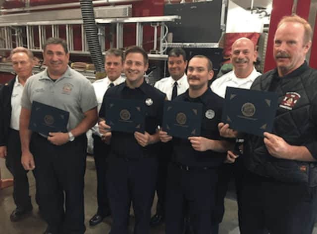 Front, L-R, Capt. Shaun Tripodi, firefighters Keven O'Brien, Kevin Campbell and Richard Walsh with their award in aiding a man. Back, L-R, Assistant Chief Robert Morris, Asst. Chief Mike Robles, Chief Trevor Roach and Deputy Chief Patrick Tripodi.