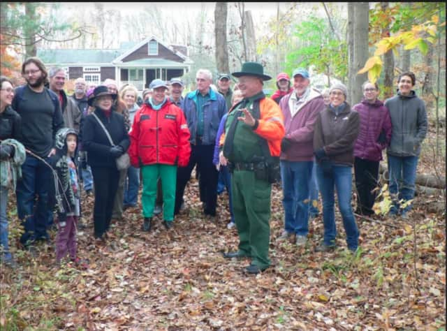 David Solek, right. (in green), Monroe's park ranger and tree warden, addresses  his hiking group during the Monroe Halloween Fall Foliage Creepy Cemetery Tour.