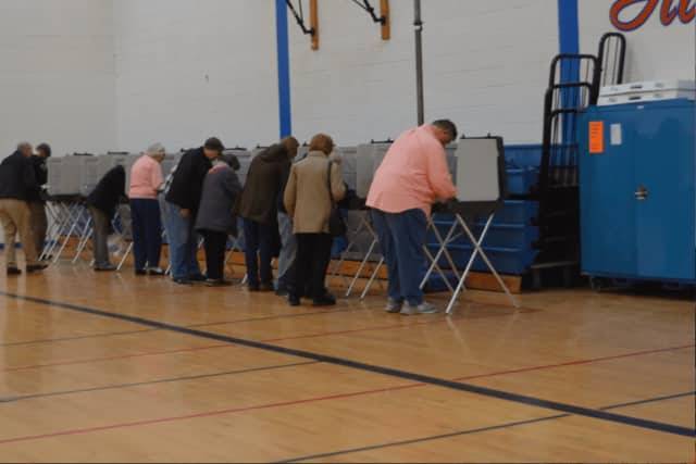 A steady stream of voters casts ballots on Tuesday in the gym at Danbury High School.
