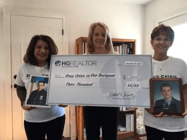 Carol Christiansen, left, and Susan Salomone, co-founders of Drug Crisis in Our Backyard, hold photos of the sons they lost to drug addiction. Lin Crispinelli of Hudson Gateway Association of REALTORS®, displays a facsimile of the $3,000 check.