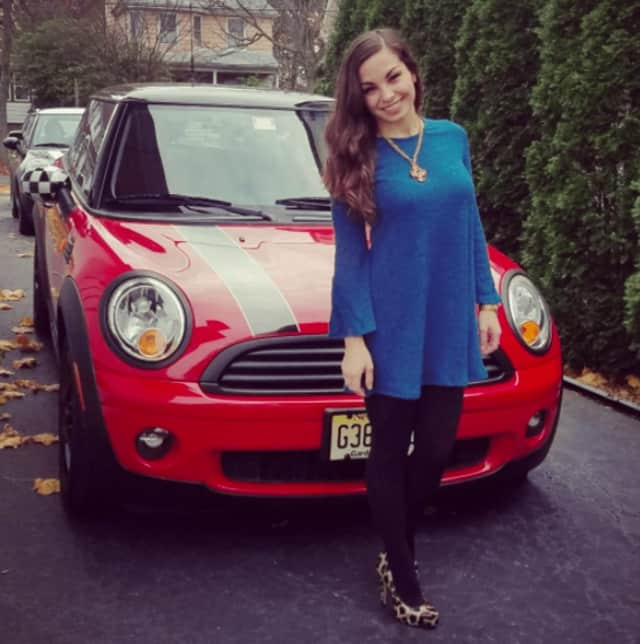 Brittany Tierney of Teaneck and her Mini Cooper. Mini Cooper owners will deliver toys from Prestige Mini in Ramsey to kids at the Audrey Hepburn Children's House in Hackensack.