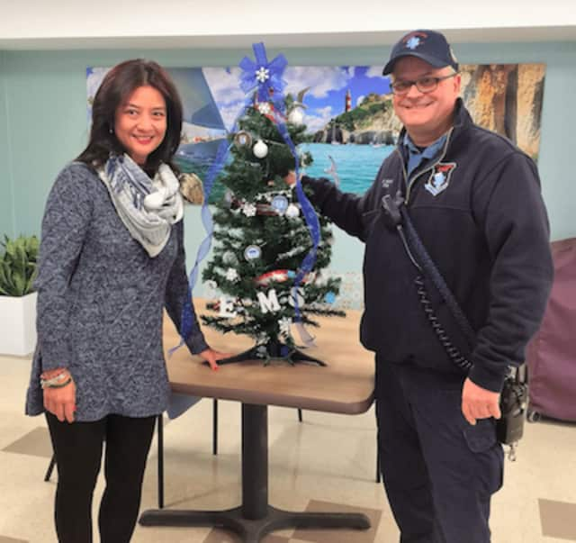 Stamford EMS Paramedic Mike Mansi presents a donated Stamford EMS tree to Minette Zambo of the Cassena Care of Stamford during the third annual Festival of Trees.
