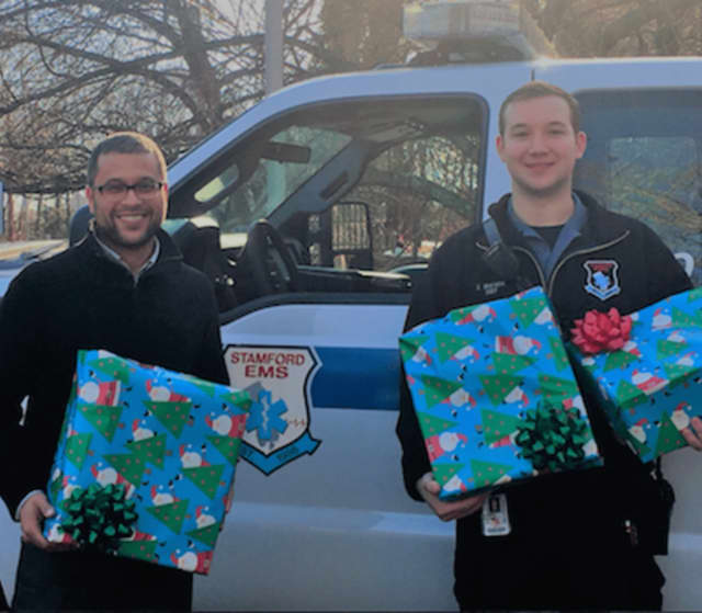 SEMS EMT, Zachary Ramon (right) presents DCF Case Worker Ramon Sanchez with gifts for nine children, and one pregnant mom.