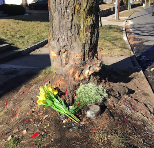 Flowers mark the site where a truck slammed into a tree on Hope Street early Saturday claiming the lives of two young men, Stamford Police said. A third man was treated and released from hospital.