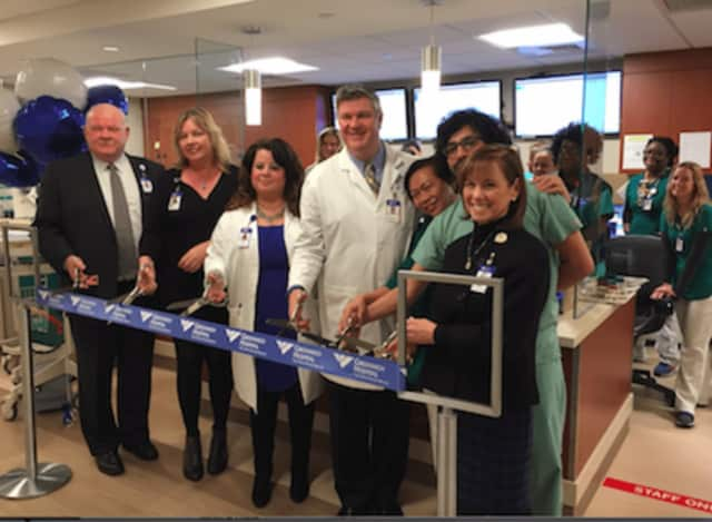 Norman Roth (left), president of Greenwich Hospital, and Susan Brown. RN, MSN (right), executive vice president for Operations, flanked by Emergency Department staff at a ribbon cutting event to celebrate a multi-million dollar renovation.