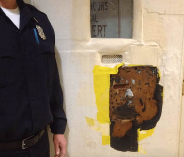 A police officer stands by the door of a padded Stamford Police holding cell that was damaged by a man facing arrest for assaulting a restaurant manager late Tuesday.