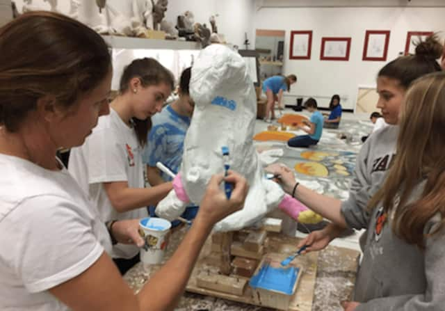 Stamford-based artist Paige Bradley, at left, and Greenwich Country Day students working on the Alice in Wonderland theme set for Kids in Crisis fundraiser.