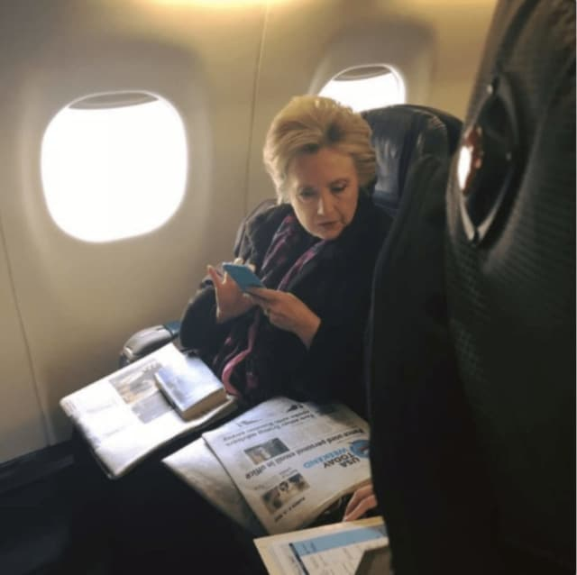 A passenger on a New York City-bound flight from Boston snapped this photo of Hillary Clinton reading a newspaper story about Vice President Mike Pence's use of personal email. The passenger posted the photo on Twitter.