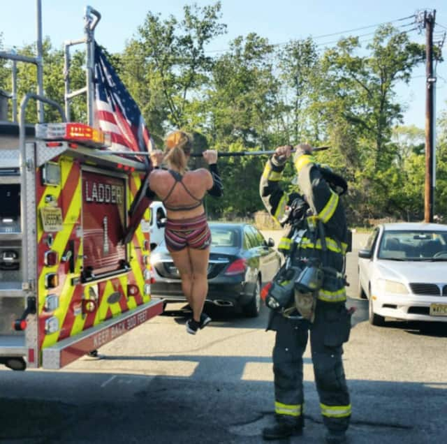 Kirin Hart bangs out some pull ups on a Hackensack fire engine when her gym's power went out.