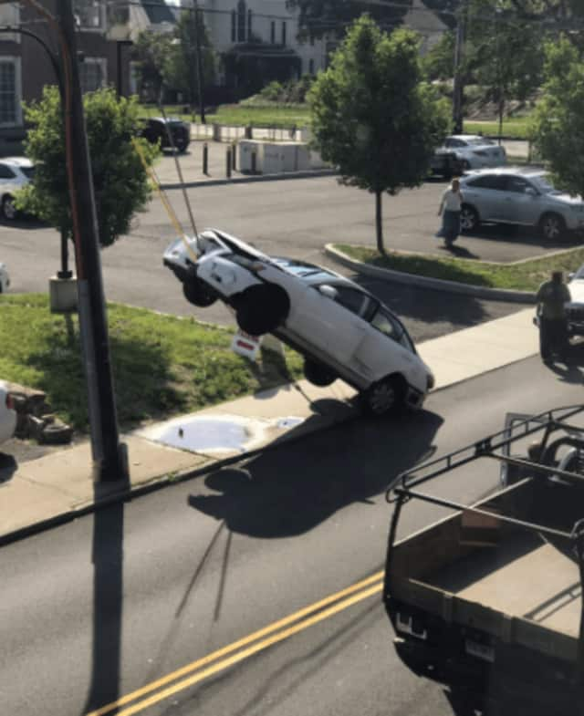 A car is impaled on an electric wire on New Street after a crash Tuesday morning in Danbury.