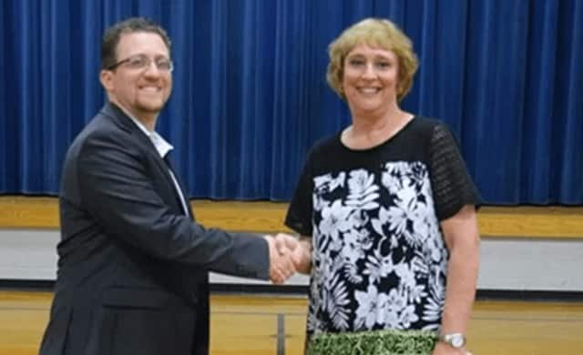 Scott Clough, left, the new principal at St. Mark School in Stratford, shakes  hands with his predecessor, Donna Wuhrer, who retired from the position after three years as school leader.