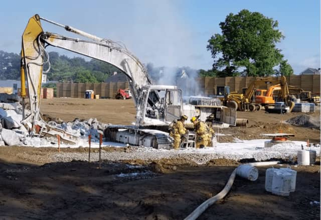 Fire crews used foam to put out a burning excavator at the Home Depot construction site in Stamford on Saturday morning.