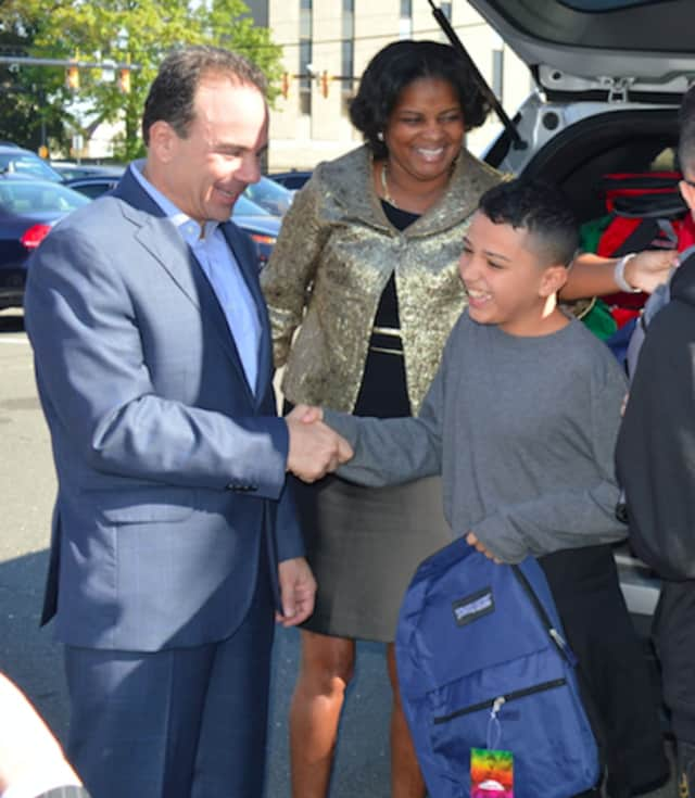 Bridgeport Mayor Joe Ganim and Schools Superintendent Aresta Johnson present Juan Casiano of Puerto Rico with a new backpack as he gets ready to attend school in Bridgeport. New Canaan has also enrolled students from the hurricane-ravaged area.