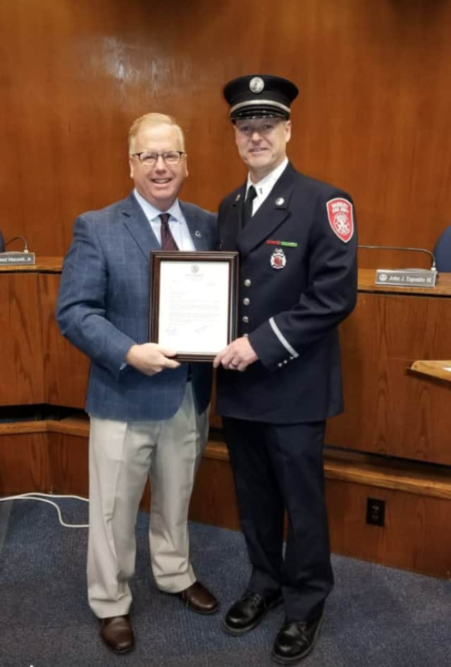 Bart McCleary, a 30-year member of the Danbury Fire Department, is congratulated on his promotion to captain by Mayor Mark Boughton.