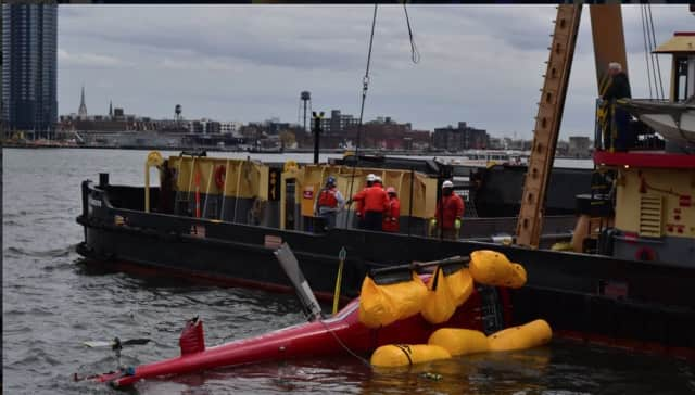 NTSB officials work to recover the helicopter that crashed Sunday near Manhattan.