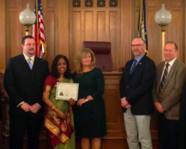 One of Putnam County's new citizens being congratulated by County Executive MaryEllen Odell, Sheriff Robert Langley and other elected officials at a recent ceremony.
