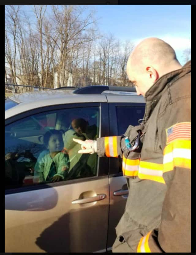 Lt. Nick Cabral trying to get the attention of the baby girl as his Engine 22 crew works on the other side of this minivan to unlock it