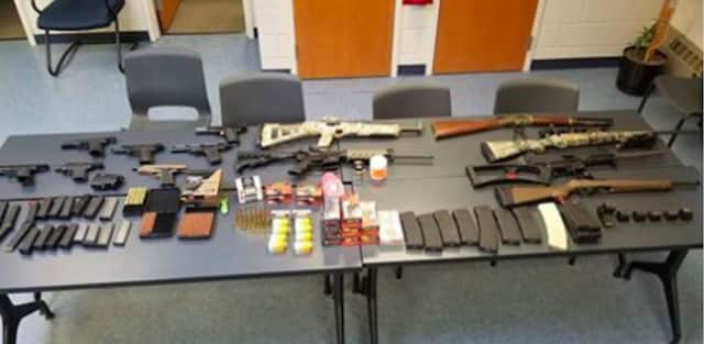 Seven handguns, six rifles, numerous high capacity magazines, ammunition, marijuana, and various firearm equipment were seized by police.